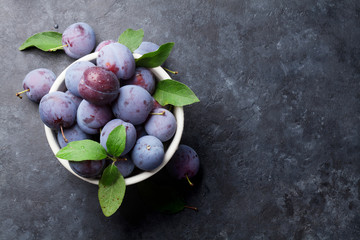 Garden plums in bowl on stone table