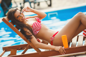 Young pretty slim beautiful girl resting at the swimming pool in the swimsuit with sunscreen cream wearing sunglasses. Cheerful woman relaxing and tanning