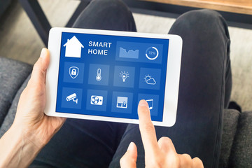 Hands touching smart home automation assistant screen on tablet, interior