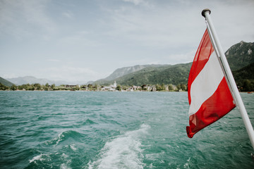 Austrian flag above the wake of a boat on a lake