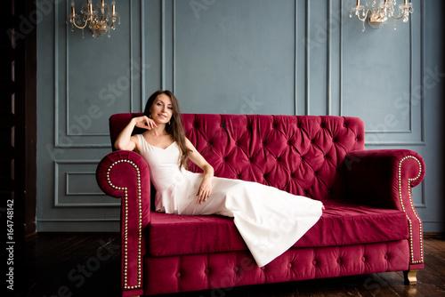 Красивая девушка на красном диване