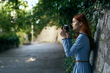 Young beautiful woman in blue dress walking with her camera around the city