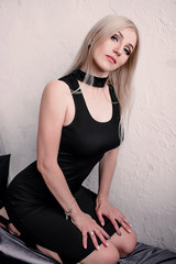 Elegant fashionable sensual blonde middle aged woman in black dress