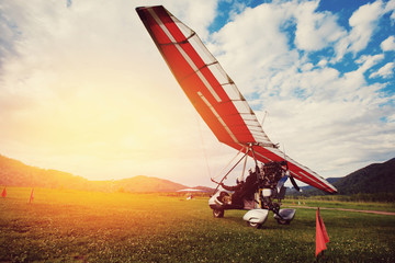 paraglider with a motor is standing on the ground, preparing for take-off. Against the backdrop of the mountains and sunset with glare. The concept of extreme entertainment