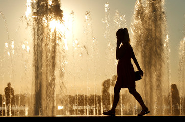 Woman is silhouetted in front of a fountain during sunset in Samara