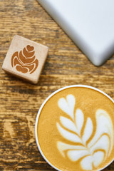 Coffee foam top view. Wooden cube with flower picture. Latte art basics.