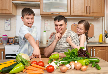 Father and two children in home kitchen interior. Happy family, girl and boy having fun with fruits and vegetables. Healthy food concept.