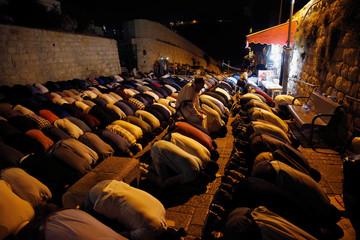 Palestinians take part in evening prayers outside the Lion's Gate of Jerusalem's Old City