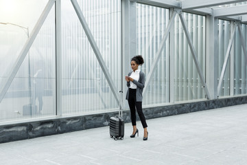 Businesswoman standing in airport terminal, checking mobile phone