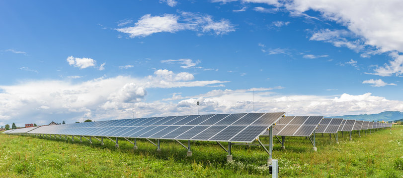 Panels of the solar energy plant under the blue sky with white clouds - clean energy concept