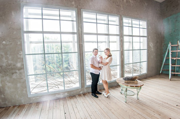 Beautiful mum and dad in white stand at the window with a small daughter