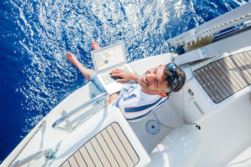 Man with laptop computer on sailboat