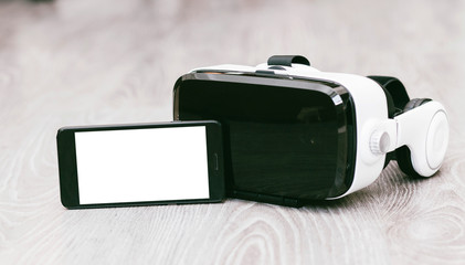 VR Glasses or Virtual Reality Headset helmet with phone wood background