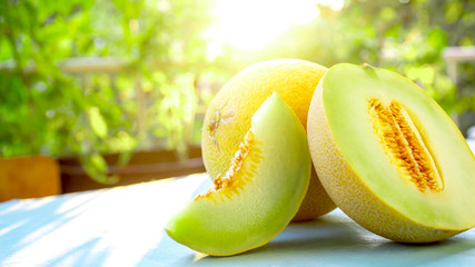 Cantaloupe melon slices on wooden table at sunset