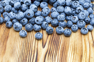 Close-up photo of fresh natural organic blueberries on brushed wooden background.  Place for text