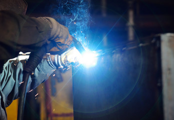 Welder for his work. Welding sparks on production background