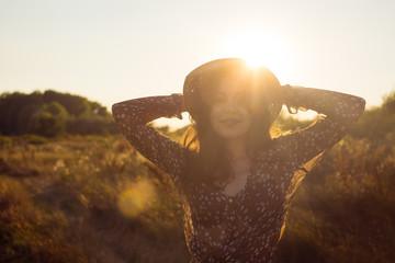 Beautiful hippie girl portrait in golden sun flare