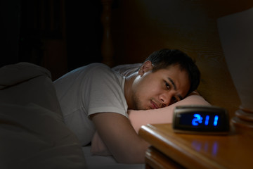 Depressed man suffering from insomnia lying in bed