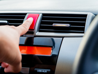 Close up, man hand push emergency light button in car.