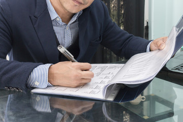 Businessman makes a note at business document