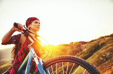 Woman tourist on a bicycle at top of mountain at sunset outdoors during  hike in summer