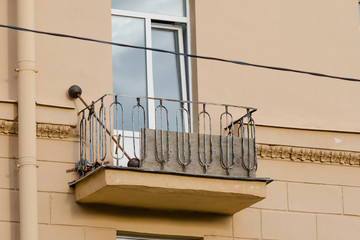 Three windows in a row and balcony on facade of urban apartment building front view, St. Petersburg, Russia
