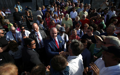 Premier John Horgan shakes hands with a supporter from the front steps of the BC Legislature during an open house following the invite-only swearing-in ceremony at Government House in Victoria