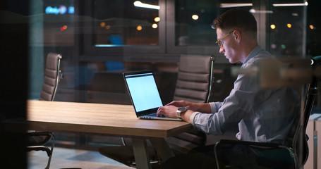 man working on laptop in dark office