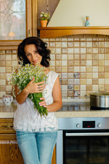 Beautiful Mature woman with a bouquet of daisies standing in the kitchen.