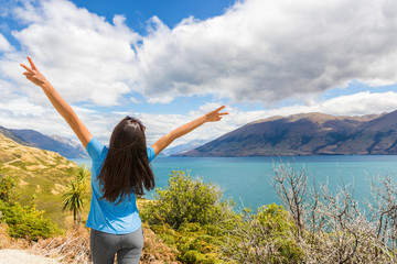 Fototapete - New Zealand travel happy tourist woman with arms up at Wanaka lake nature landscape outdoors. Wanderlust adventure young girl with peace hand sign.