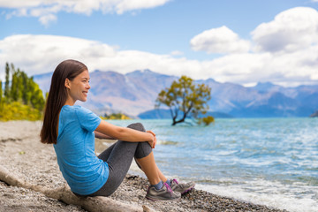 Wall Mural - New Zealand Wanaka lake nature landscape travel woman traveler. Asian tourist relaxing enjoying view from beach shore at Wanaka lake landscape with lone tree, famous attraction.