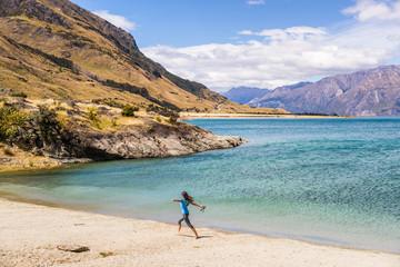 Wall Mural - New Zealand travel happy tourist woman running of joy and freedom at beach shore of lake Hawea nature landscape. Near Wanaka, Otago Region