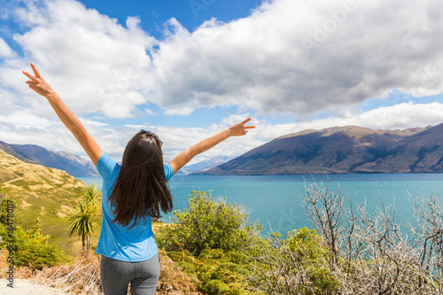 Wall mural New Zealand travel happy tourist woman with arms up at Wanaka lake nature landscape outdoors. Wanderlust adventure young girl with peace hand sign.