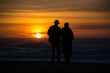 Elderly Couple holding each other in front of waves and sunset on the coast.