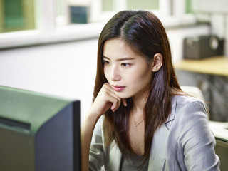 asian business woman working in office using desktop computer