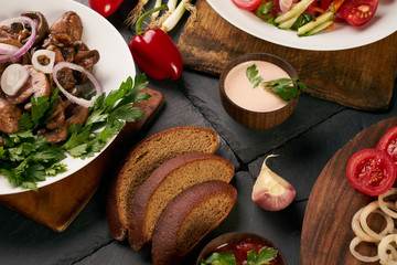 Set of three bowls with different dishes: fried mushrooms, fresh low-calories salad with vegetables and grilled chicken breast. Fresh dietary rye bread and branded sauce on dark stone background