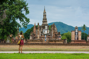A traveler is taking photo of old Buddhist temple in Sukhothai historical park Thailand.