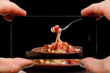 Taking photo of pasta by smartphone. Closeup view of process. File contains clipping paths for smartphone and hands and picture on it.