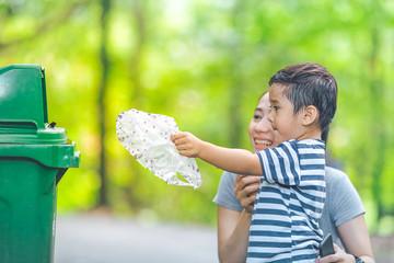 Cute little boy are dumping trash in a recycle bin