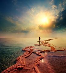 Fototapete - Woman walking on Dead Sea salt shore towards the sun