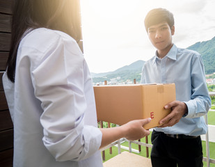 Delivery man holding a box or parcel delivered to customers. using the transport service in transport and logistics concept.