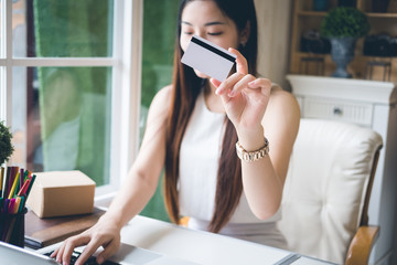 Happy young asian woman doing online shopping at home