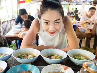 Asian woman eating noodle in Thai local restaurant.