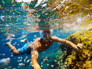 Playful man making selfie underwater with action camera.