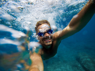 Energy man with smile taking a selfie photo underwater during summer.