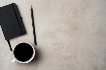 Office desktop with coffee cup, pencil and notebook