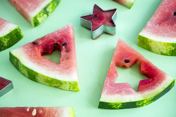 Watermelon slices and carved shape shapes on a green background