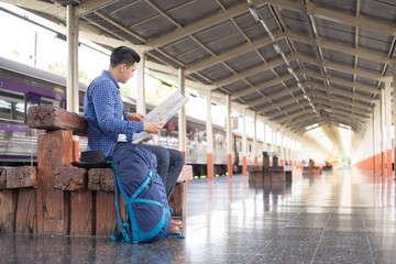 man traveler with backpacker look searching location map at trainstation