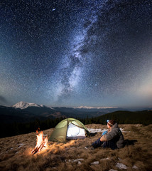 Male tourist have a rest in his camp at night. Man with a headlamp sitting near campfire and tent under beautiful sky full of stars and milky way. On the background snow-covered mountains and forests