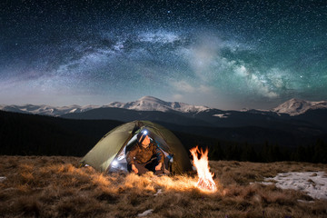 Male tourist have a rest in his camping in the mountains at night. Man with a headlamp sitting near campfire and tent under beautiful night sky full of stars and milky way, and enjoying night scene Wall mural